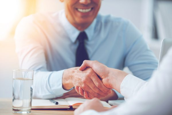 Verbal Agreement of two people shaking hands at a table